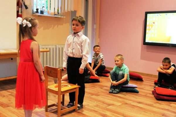 Мальчик и девочка разыгрывают сценку, дети наблюдают