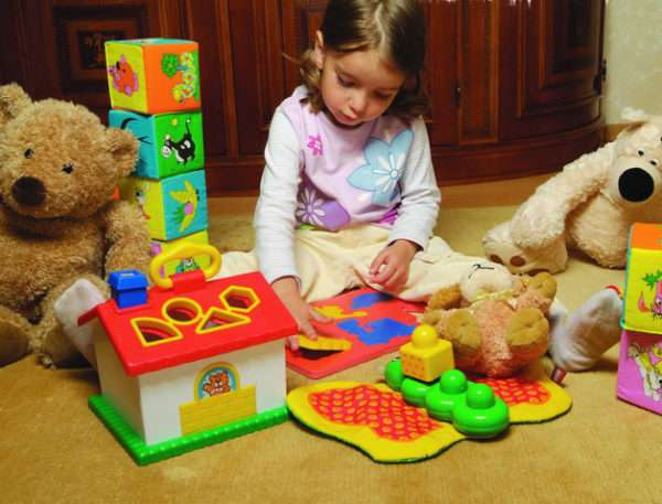 Девочка играет с яркими игрушками