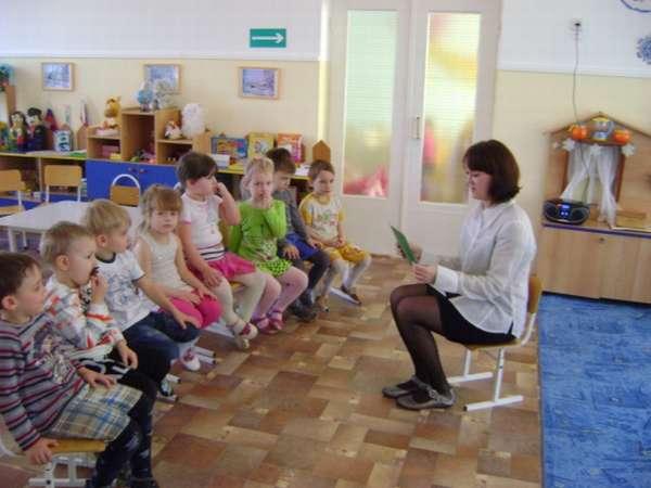 Педагог читает детям, сидящим напротив