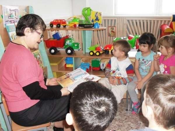 Воспитатель читает книгу в младшей группе