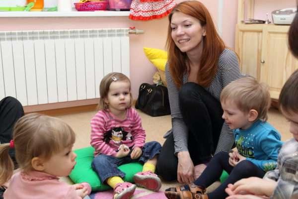 Воспитательница что-то рассказывает детям