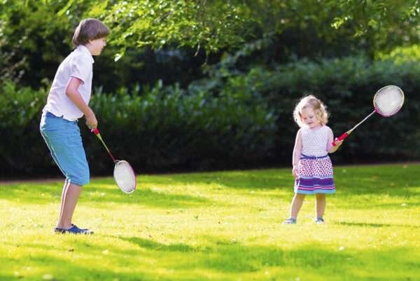 Мальчик и девочка играют в бадминтон