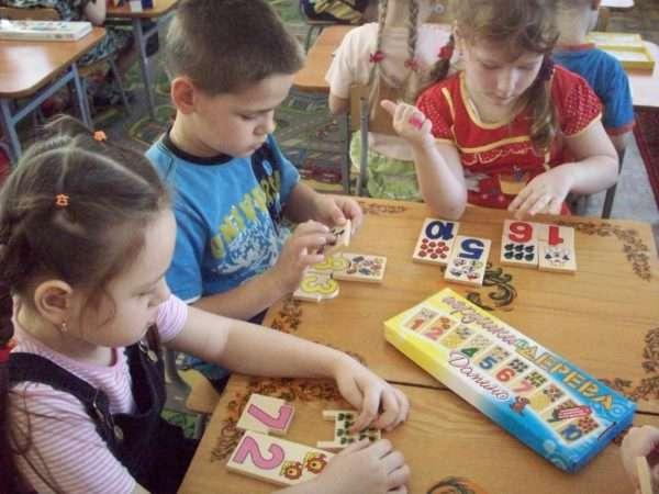 Две девочки и мальчик соотносят таблички с цифрами с требуемым количеством предметов