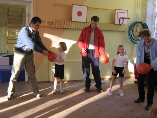 Дети и родители передают друг другу мячи
