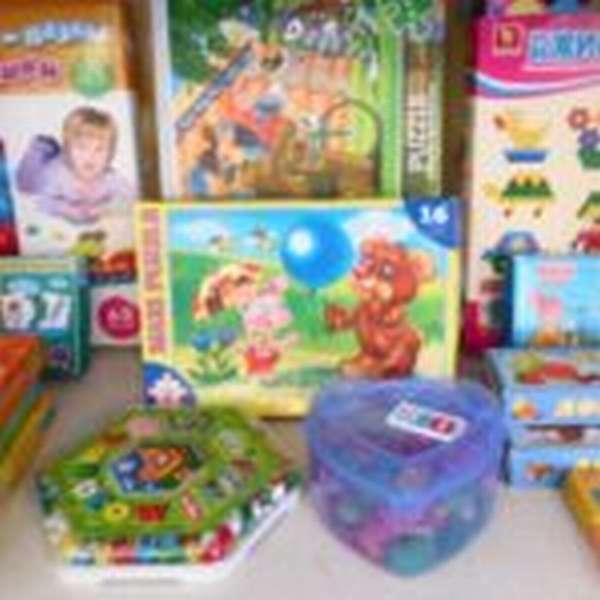 На столе расставлены коробки с настольно-печатными играми