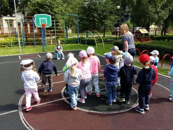 Воспитатель на спортивной площадке рассказывает детям условия игры
