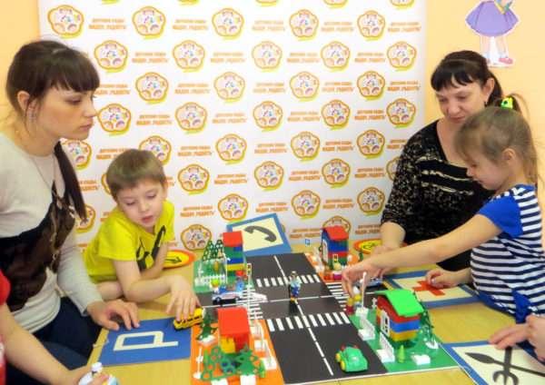 Дети и родители рассматривают макет города с дорожными знаками
