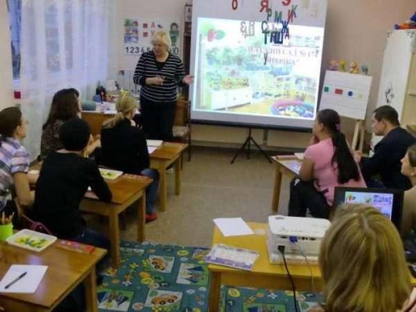 Воспитательница презентует свой опыт на экране перед сидящими за столами коллегами