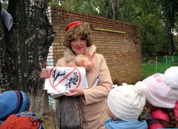 Педагог в костюме Лисы Алисы показывает детям запрещающий знак