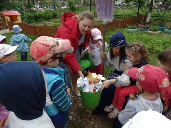 Дети рассматривают ведро с мусором