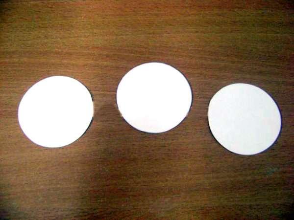 Три белых кружка лежат на столе