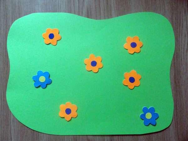 Оранжевые и голубые цветочки разложены на зелёном листе бумаги
