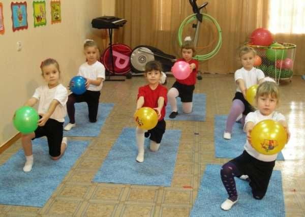 Дети на ковриках с мячами