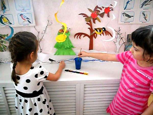 Две девочки раскрашивают весенний уголок
