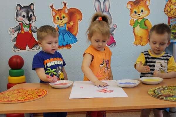 Дети делают отпечатки ладошек на листе бумаги