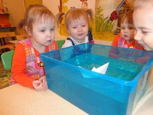 Дети наблюдают за корабликом, находящемся в ёмкости с водой