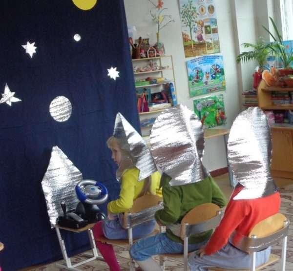 Трое детей, сидя на стульях, играют в космическое путешествие