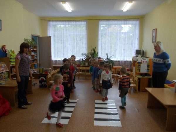 Дети в группе шагают по двум полосам нарисованного пешеходного перехода