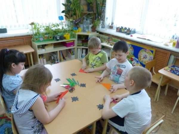 Дошкольники сидят за столом и складывают оригами из бумаги