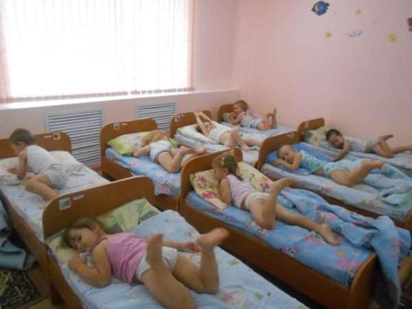 Дети, лёжа в кроватях, машут ногами