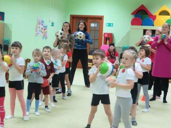 Дети и родители с мячами в руках выстроились в две шеренги