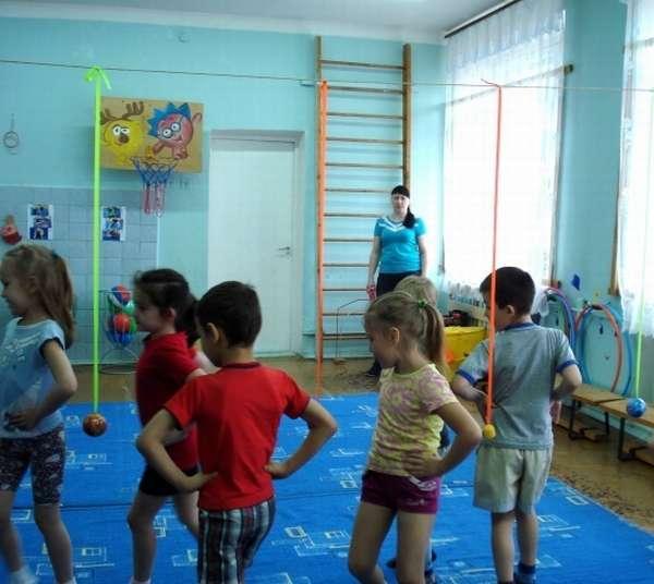 Дети шагают между ленточек с мячиками
