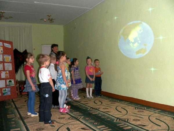 Дети и воспитатель смотрят на изображение Земли на стене