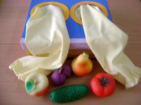 Синяя коробочка с тканевыми рукавами, рядом лежат муляжи овощей и фруктов