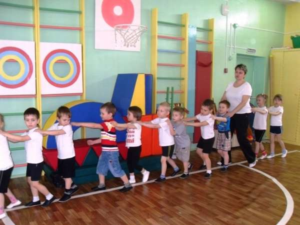 Дети и педагог идут паровозиком
