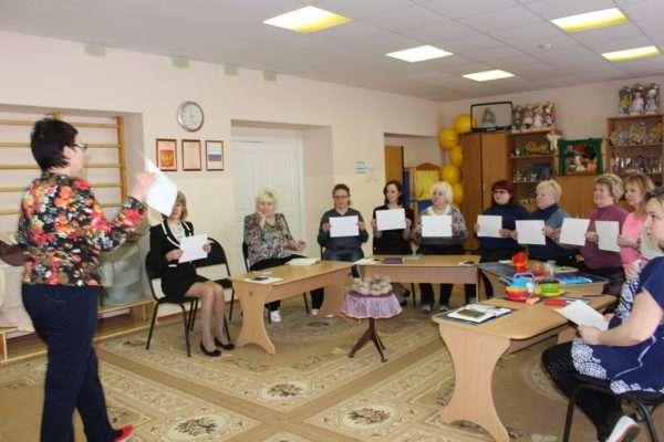 Воспитательница показывает мастер-класс, коллеги держат листы бумаги перед собой