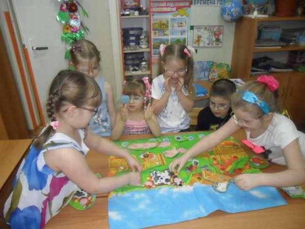 Девочки в очках играют в настольную игру