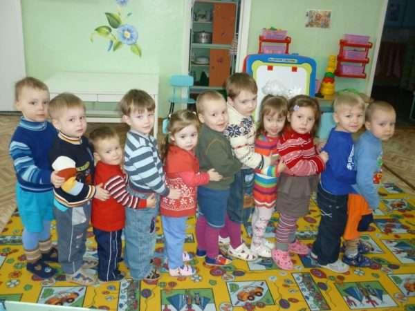Одиннадцать детей стоят в паровозике в группе