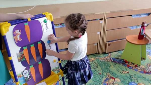 Девочка крепит цифры к картинкам с морковками на магнитной доске