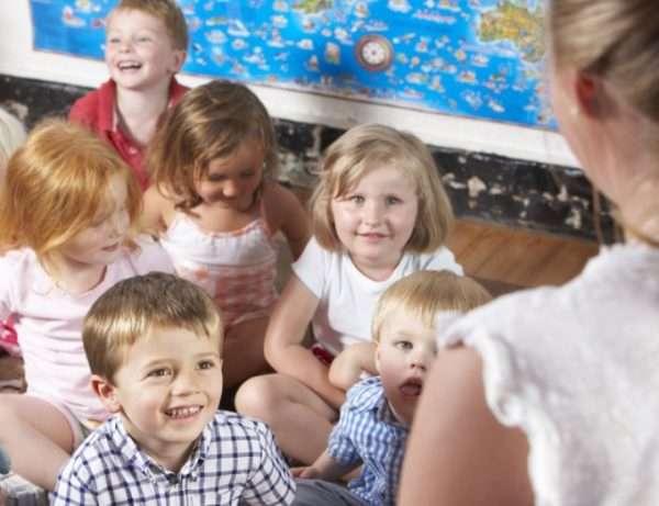 Педагог беседует с улыбающимися детьми