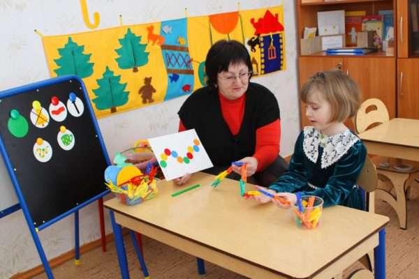 Педагог занимается с девочкой с цветными прищепками