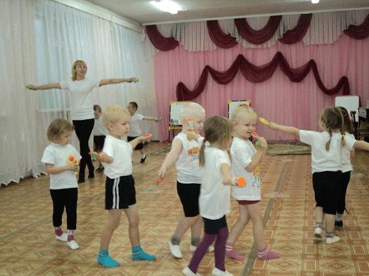 Дети и педагог ходят по музыкальному залу с погремушками в руках