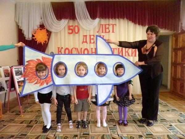 Педагоги держат большую бумажную ракету, дети смотрят в «иллюминаторы»