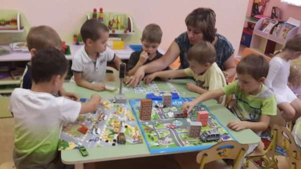 Дети с воспитательницей играют машинками по игровому полю с проезжей частью