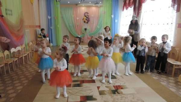 Дети в нарядных костюмах хлопают в ладоши