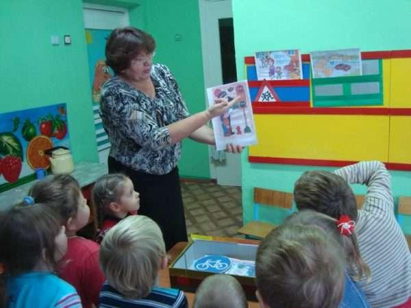 Воспитательница показывает картинку со светофором, комментирует цвета сигналов