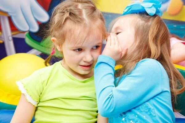 Девочка что-то шепчет на ухо другой девочке