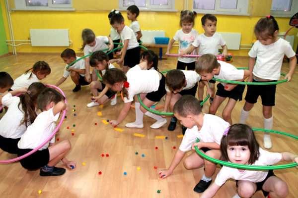 Дети собирают бусины с пола, не выходя за пределы обруча
