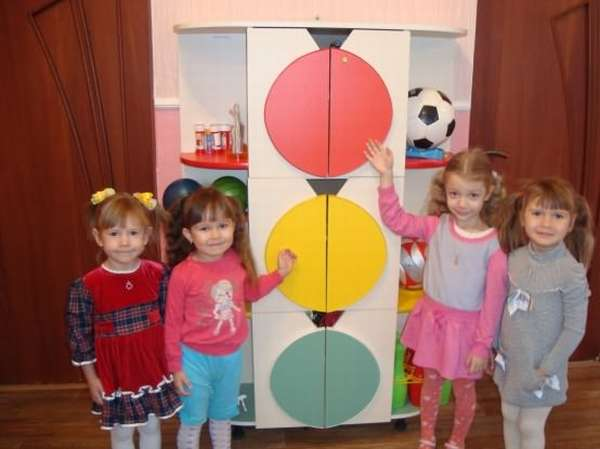 Четыре девочки стоят возле большого макета светофора