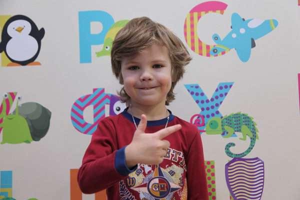 Улыбающийся мальчик на фоне плаката с буквами и картинками