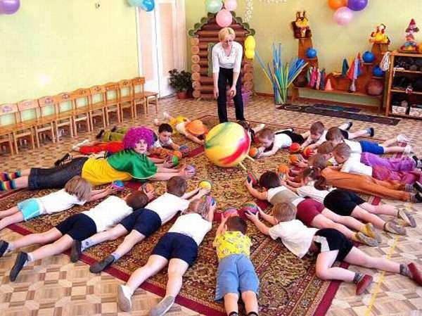 Дети и педагог в костюме клоуна тянутся к мячу