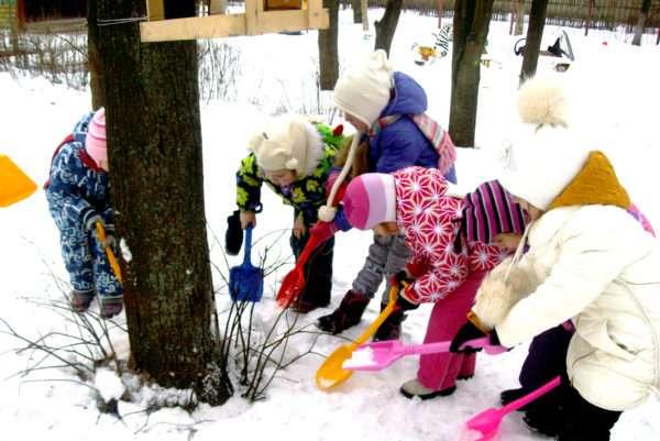 Дети лопатками копают снег вокруг дерева