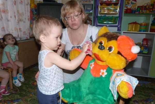 Малыш вытирает носовым платком мягкую игрушку