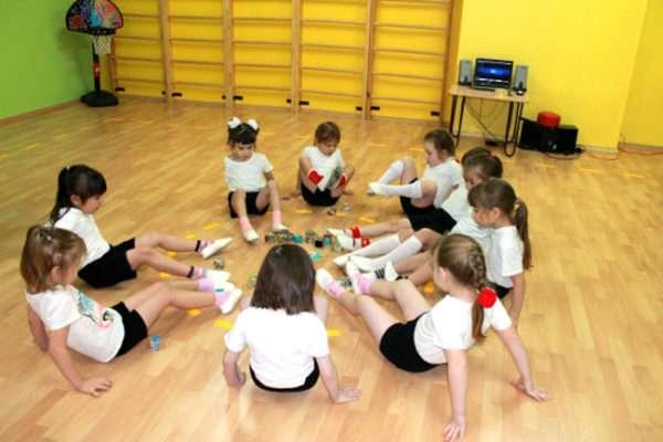 Дети выполняют упражнение, сидя на полу в спортивном зале