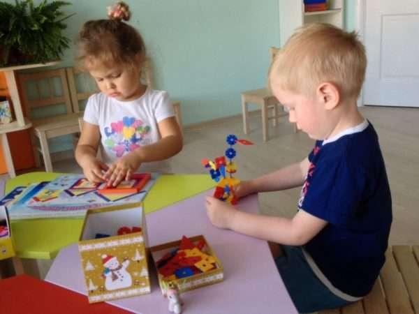 Девочка и мальчик играют игрушками для развития мелкой моторики: палочками и фигурками пирамиды