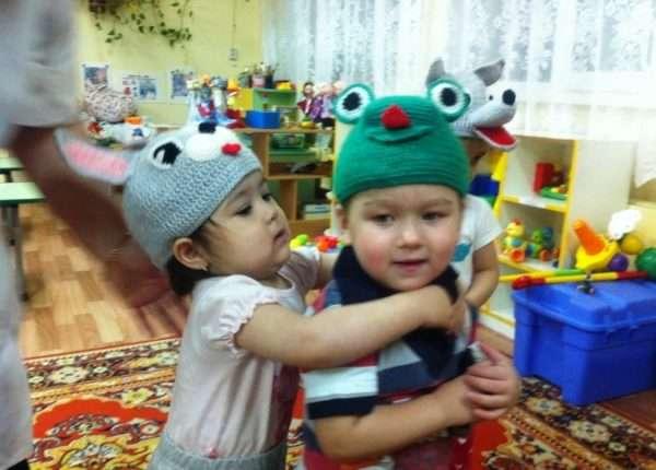 Девочка в шапочке зайца схватилась за шею мальчика в шапочке лягушки